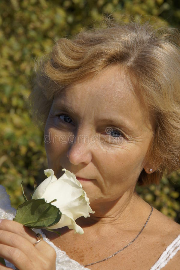 Portrait of a Woman with a rose. Portrait of a mature woman with a white rose in his hand royalty free stock images
