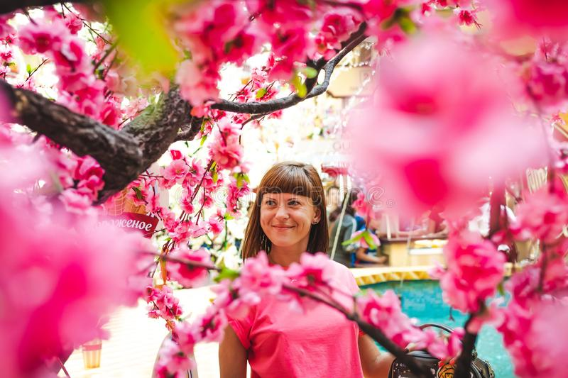 Portrait of woman among sakura tree in the shopping mall. stock photos