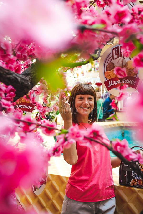 Portrait of woman among sakura tree in the shopping mall. stock image