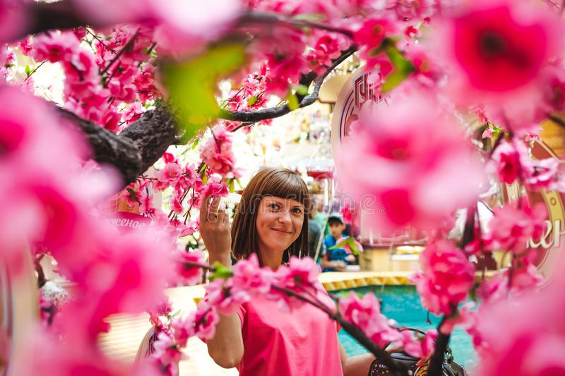 Portrait of woman among sakura tree in the shopping mall. royalty free stock image