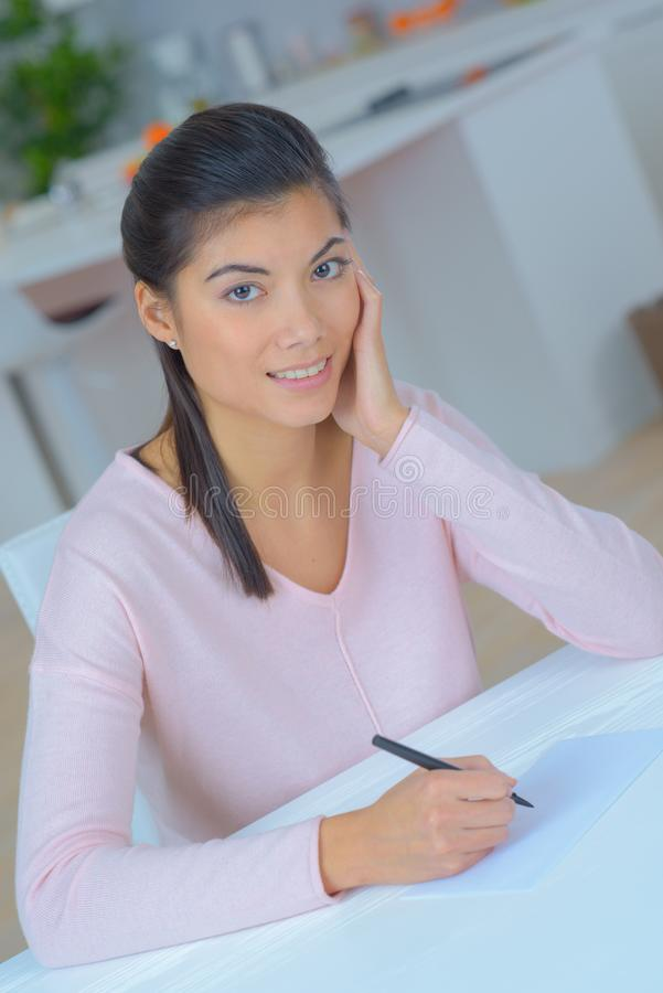 Portrait woman sat writing at home stock photos