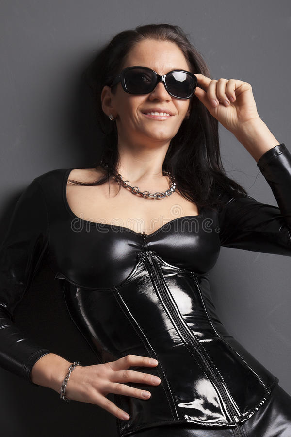 Portrait of a woman in shiny rubber. Woman in shiny latex rubber corset and spandex catsuit stock images