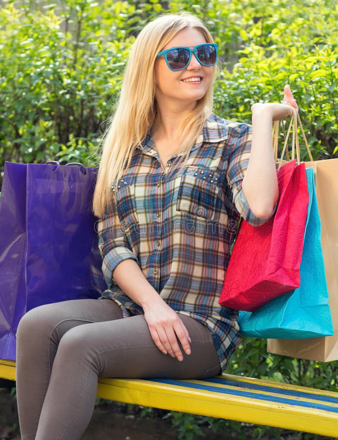 Portrait of a woman with shopping bags on the bench royalty free stock photography