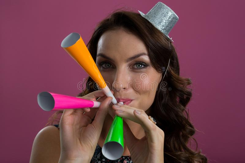 Woman in sliver hat blowing party horns stock image