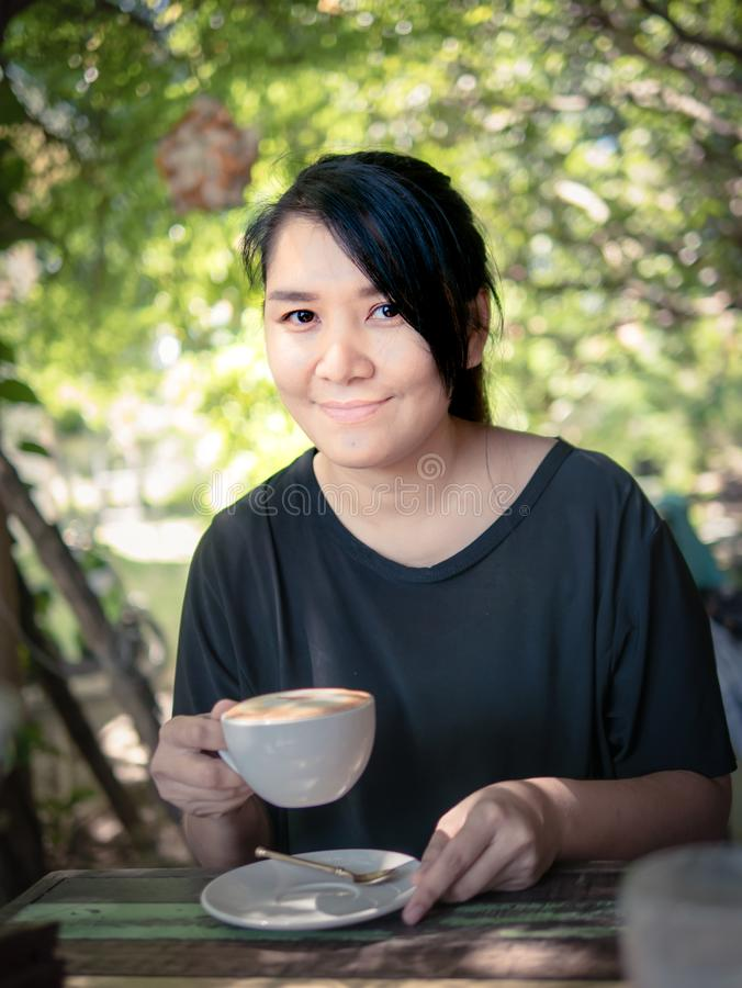 Portrait of woman smiling with a cup of hot Cappuccino royalty free stock photo