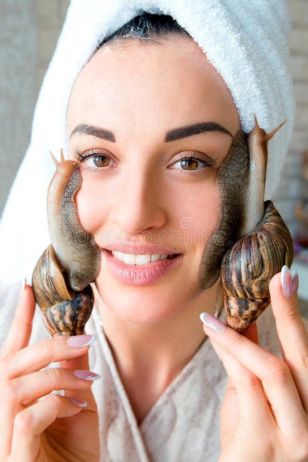 Portrait of woman with snails on her face. Portrait of smiling young darkhaired woman with snails achatina giant on her face stock image