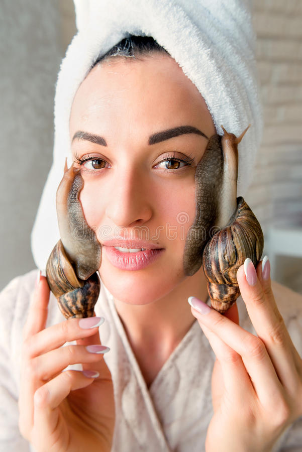 Portrait of woman with snails on her face. Portrait of young darkhaired woman with snails achatina giant on her face stock image