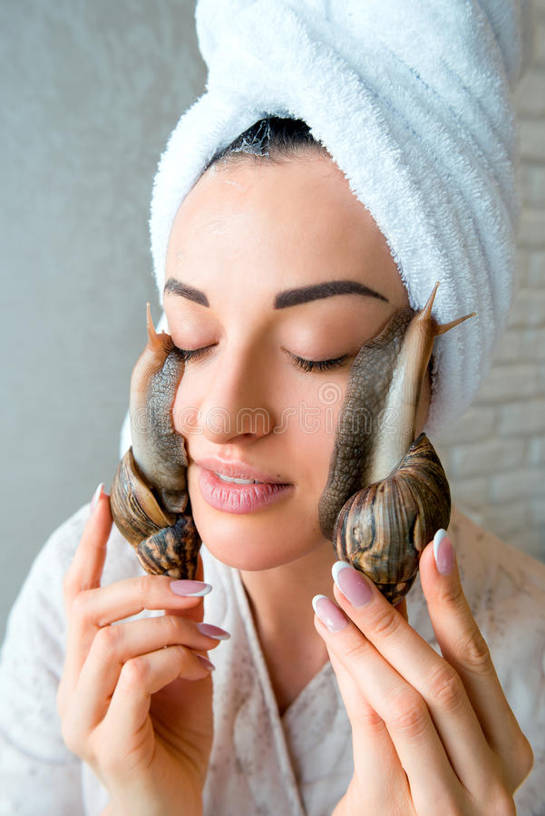 Portrait of woman with snails on her face. Portrait of young darkhaired woman with snails achatina giant on her face stock photography