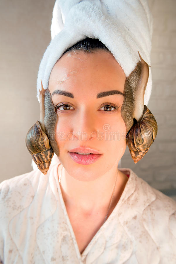 Portrait of woman with snails on her face. Portrait of young darkhaired woman with snails achatina giant on her face royalty free stock image