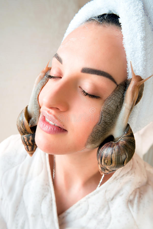 Portrait of woman with snails on her face. Portrait of young darkhaired woman with snails achatina giant on her face stock images
