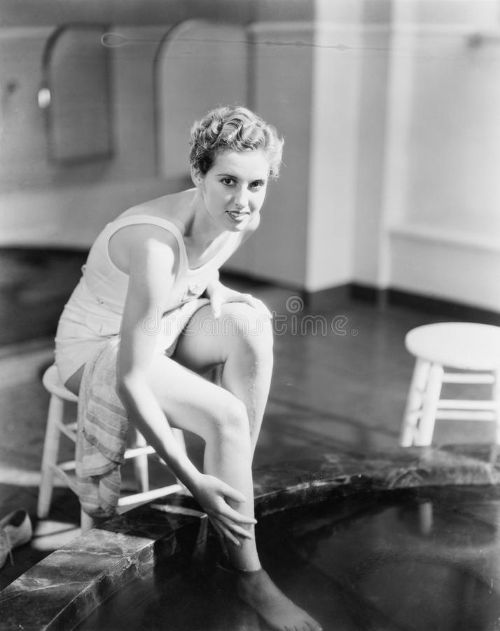 Portrait of woman soaking feet in footbath stock photos