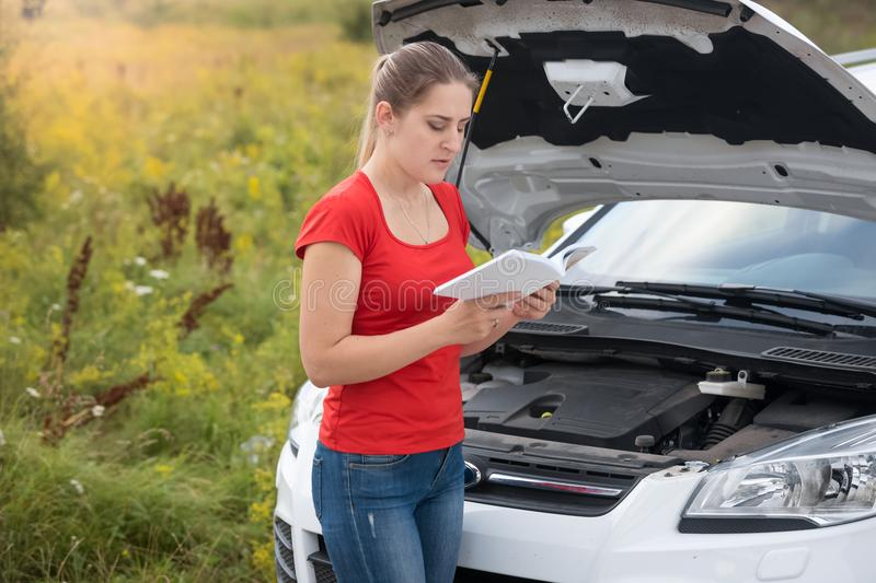 Portrait of young woman standing at broken car reading manual instruction stock images