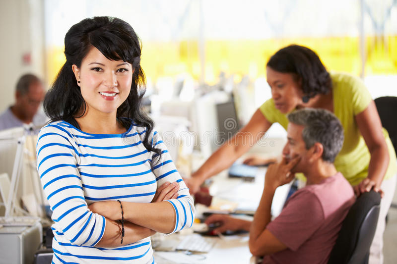 Portrait Of Woman Standing In Busy Creative Office royalty free stock image