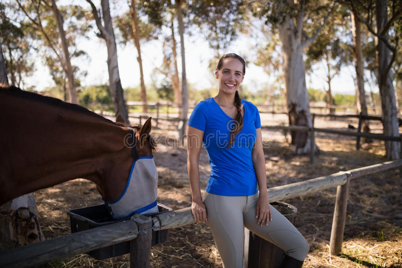 Portrait of woman standing by horse. On field at paddock royalty free stock photos