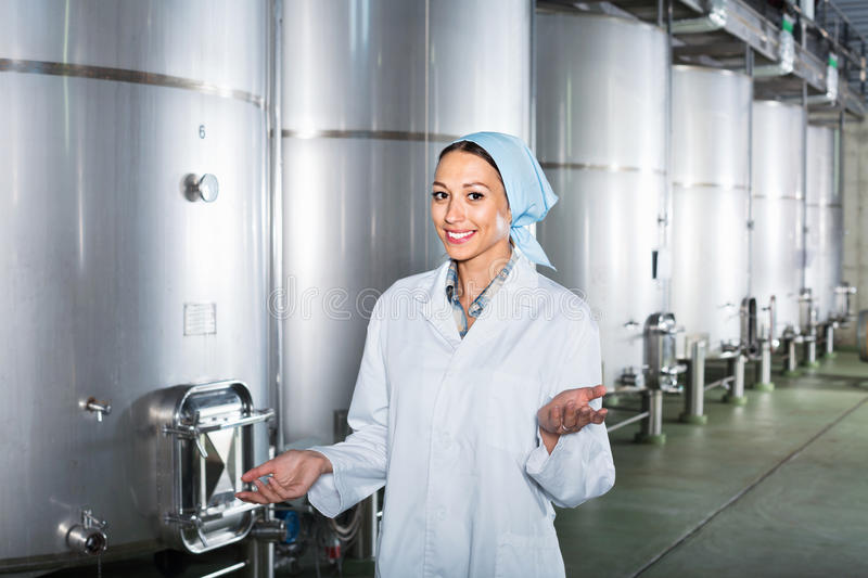 Portrait of woman standing on wine factory in secondary fermentation section. Portrait of efficient young woman standing on wine factory in secondary stock photos