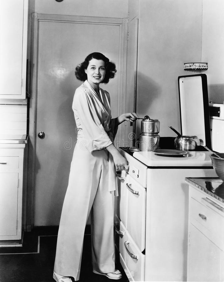 Portrait of woman at stove in kitchen royalty free stock photos