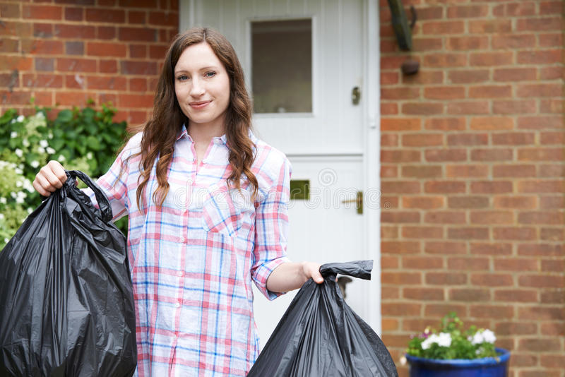 Portrait Of Woman Taking Out Garbage In Bags. Woman Taking Out Garbage In Bags royalty free stock image