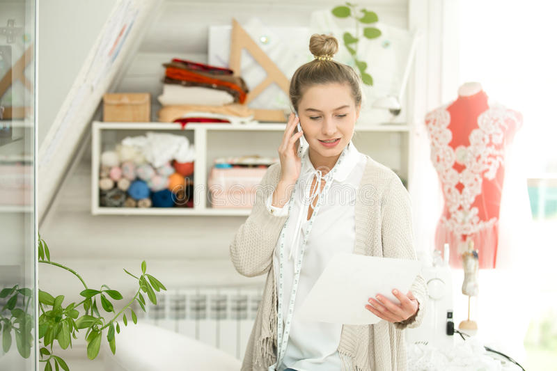 Portrait of woman talking on the phone, dressed mannequin behind stock photography
