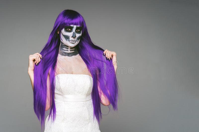 Portrait of woman with terrifying halloween skeleton makeup and purple wig hair and wedding dress over gray background looks at. The camera royalty free stock image