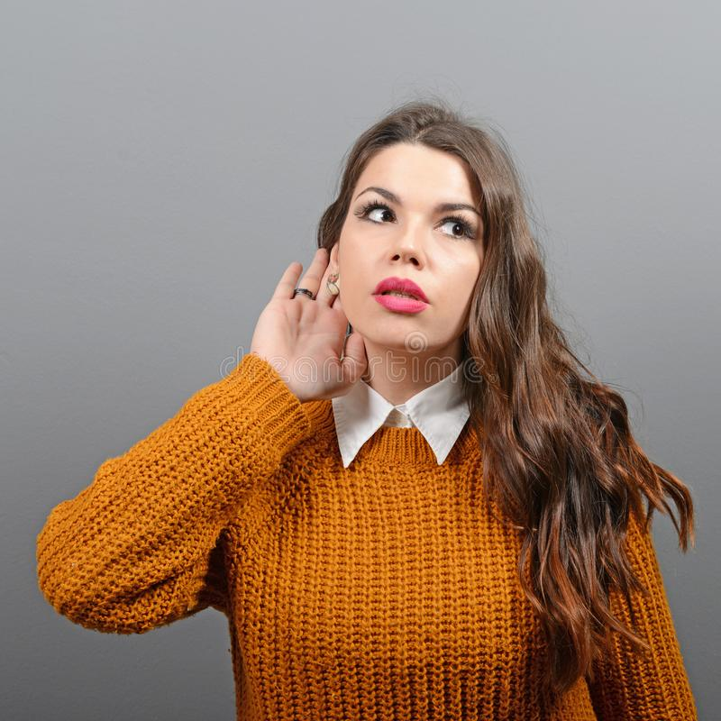 Portrait of woman  trying to listen something against gray background royalty free stock photos