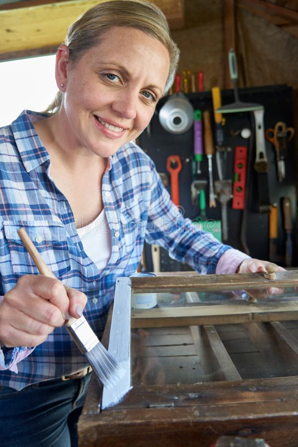 Portrait Of Mature Woman Upcycling Furniture In Workshop At Home Painting Cabinet. Portrait Of Woman Upcycling Furniture In Workshop At Home Painting Cabinet stock image
