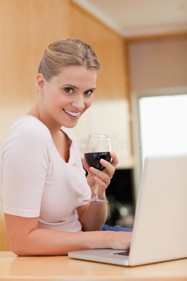 Portrait of a woman using a laptop while drinking red wine