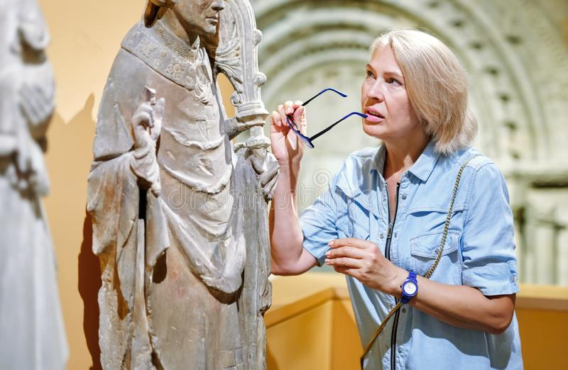 Portrait of woman visitor near sculpture in the historical museum. royalty free stock images