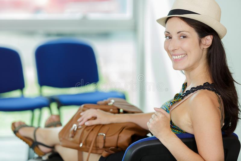 Portrait woman in waiting area feet up on suitcase royalty free stock photo