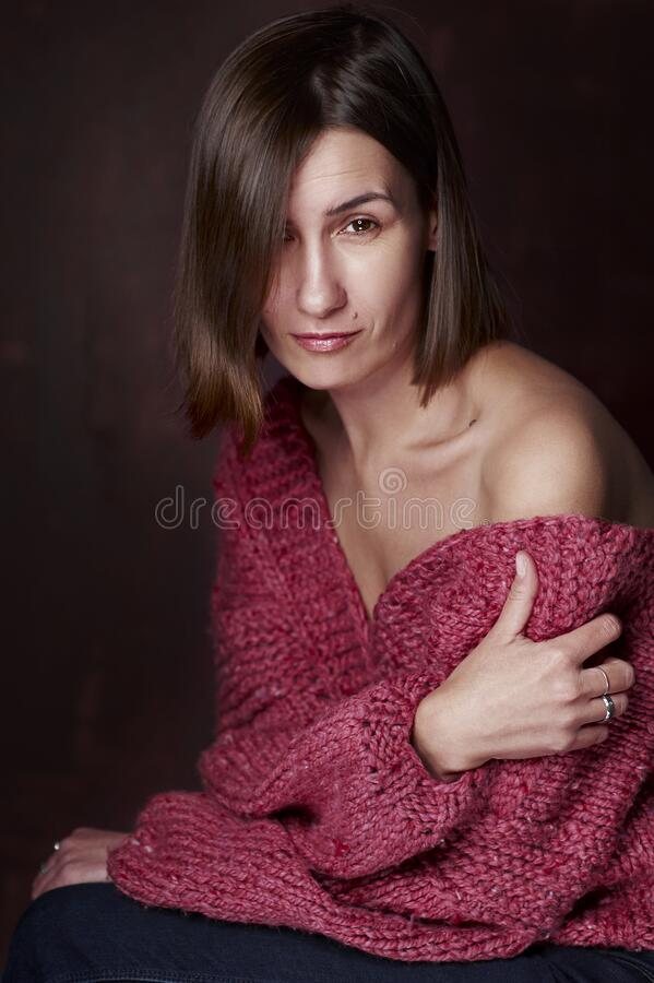 Portrait of a woman in a warm knitted sweater on a dark background royalty free stock image