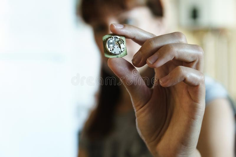 Portrait of woman watchmaker with mechanism stock image