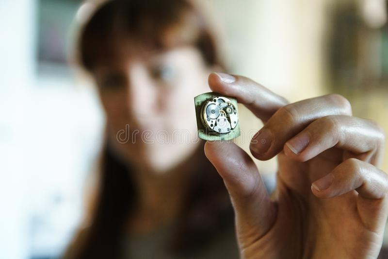 Portrait of woman watchmaker with mechanism stock photography