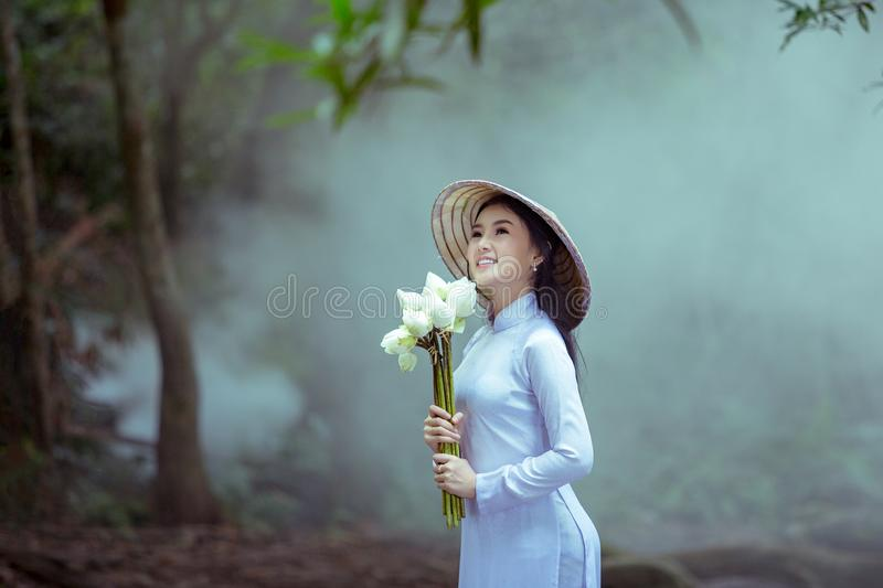 Portrait woman wearing Ao Dai Vietnam traditional dress. Holding lotus flower smiling and happiness royalty free stock images