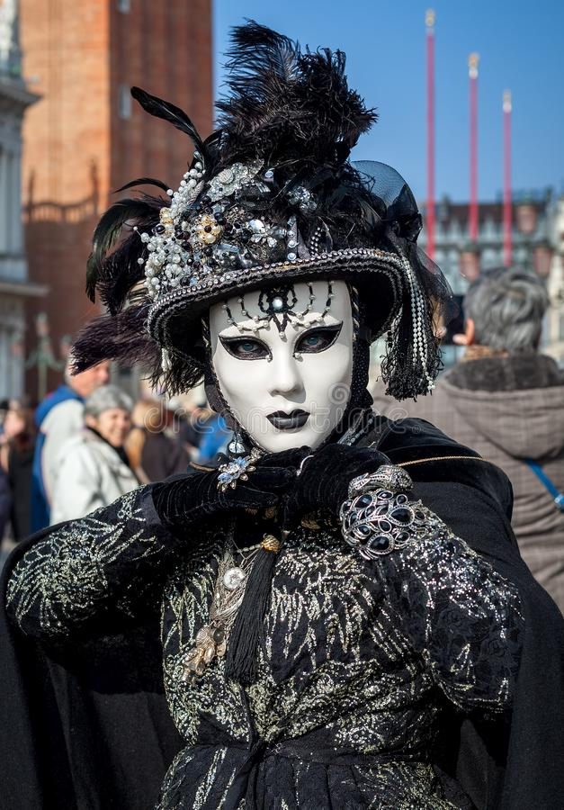 Portrait of woman wearing black costume and white mask on venetian Carnival. stock images