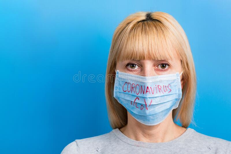 Portrait of woman wearing medical mask with nCoV word at blue background. Protect your health. concept.  stock photo