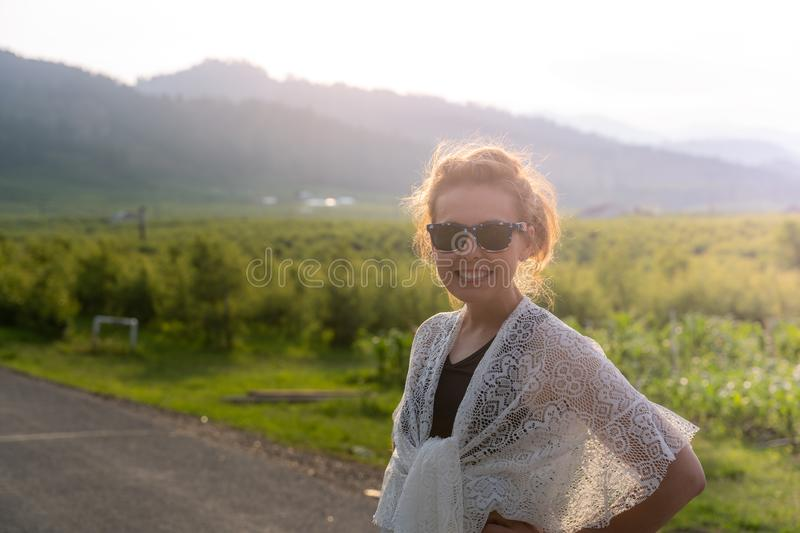 Portrait of woman wearing a white lace shawl in a rural country area. Sunflare at dusk.  royalty free stock photography