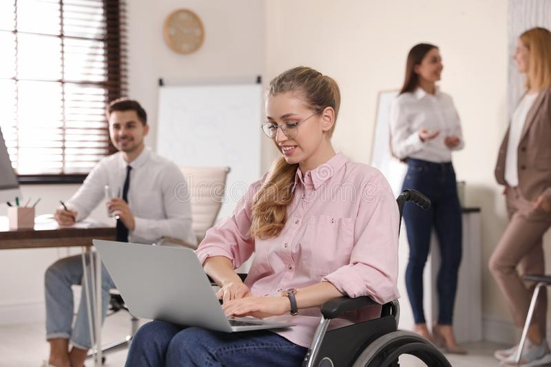 Portrait of woman in wheelchair with laptop and her colleagues. Portrait of women in wheelchair with laptop and her colleagues at workplace royalty free stock images