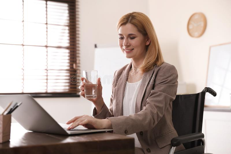Portrait of woman in wheelchair working with laptop at table stock photo