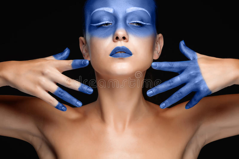 Portrait of a woman who is posing covered with blue paint stock image