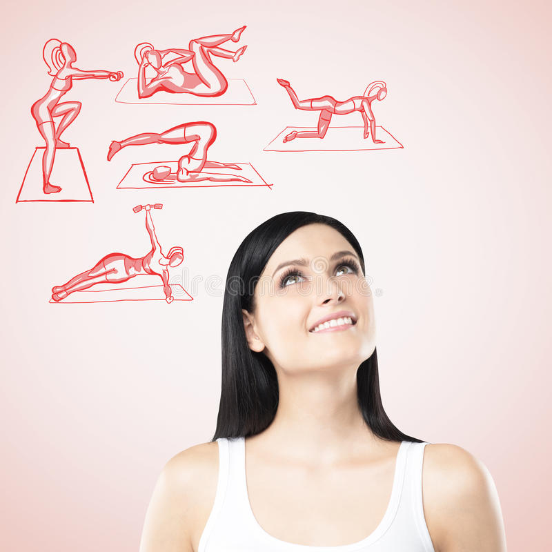 A portrait of a woman who is thinking about crossfit trainings. Cross fit icons are drawn on the pink background. A portrait of a brunette woman who is thinking royalty free stock photo