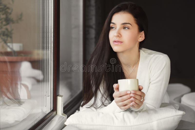 Portrait of a woman by the window with a cup of coffee. Beautiful young woman - brunette with long straight hair and gray - green eyes, wearing a white sweater royalty free stock photography