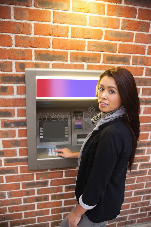 Portrait of a woman withdrawing cash. At an ATM stock photography