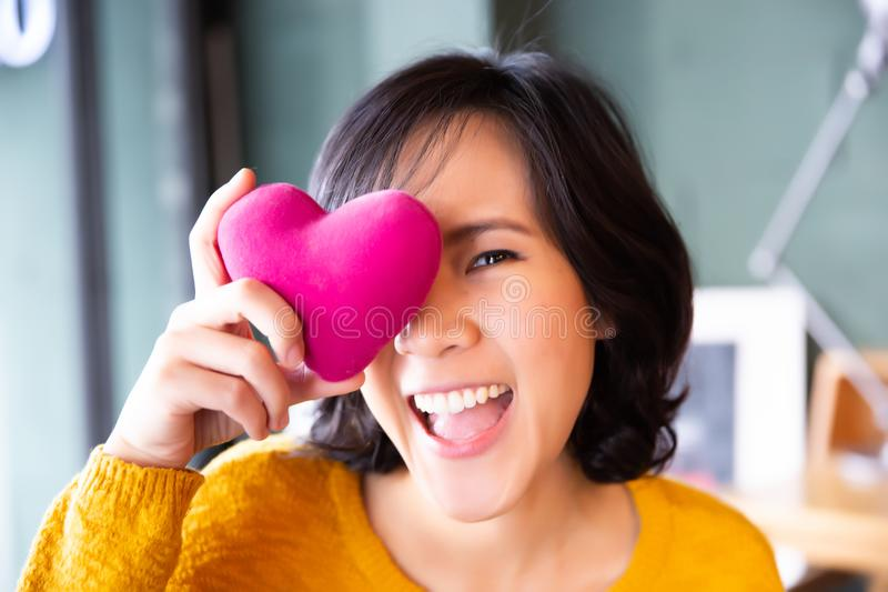 Portrait of woman in yellow sweater holding pink heart. People, age, family, love, valentine and health care concept royalty free stock photos