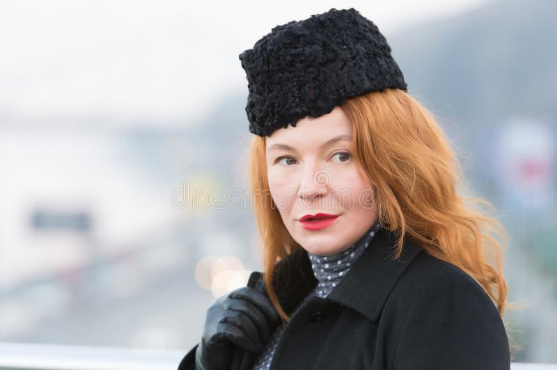 Portrait of woman in black coat and black hat. Closeup of rouge woman with red lips. Beautiful lady in coat on city background royalty free stock photography