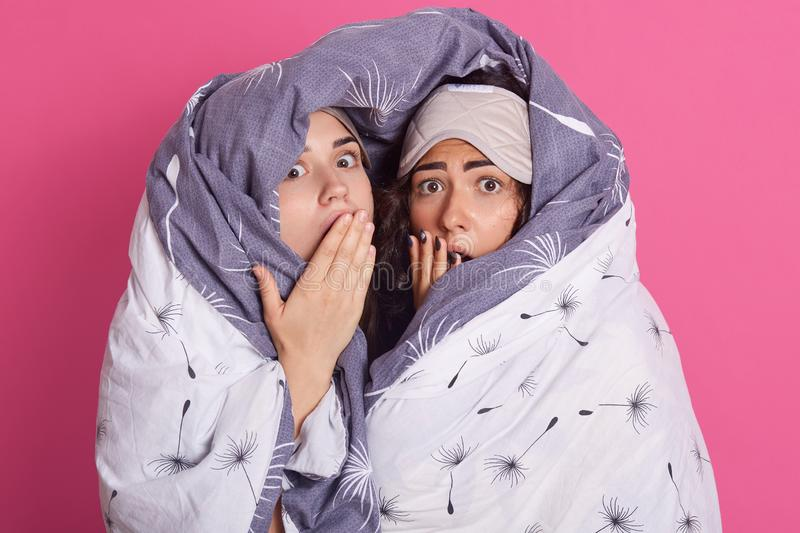 Portrait of women with blanket, posing with open mouths, keep hands near lips, looking directly at camera with shocked and scared. Facial expressions, standing stock image