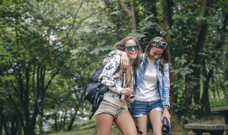 Women friends laughing while walking in forest stock photos