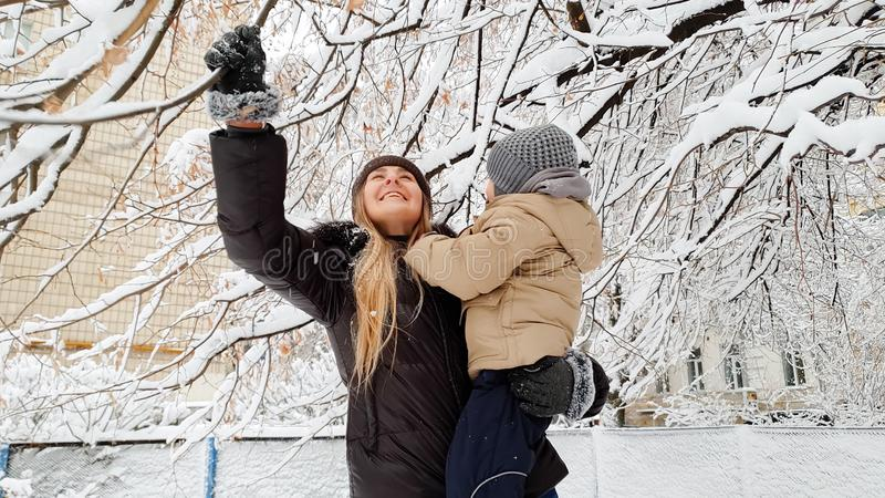 Close up portrait of woman with her cute son in jacket and hat playing with snow covered tree on the playground in the royalty free stock images