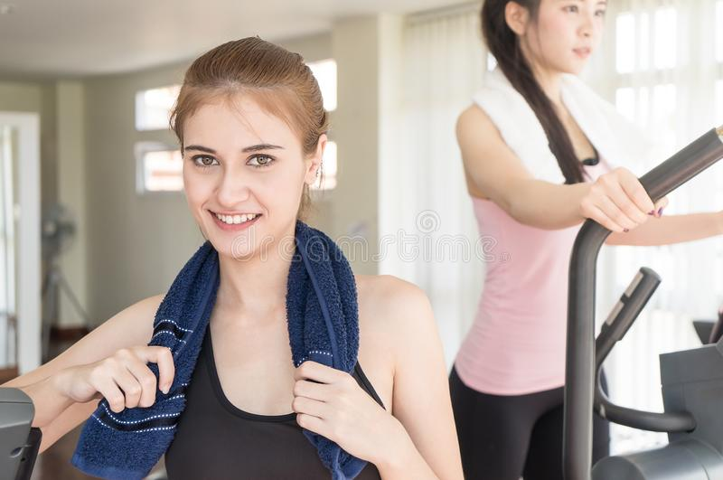 Portrait of woman in sportwear and towel training with friend stock photography