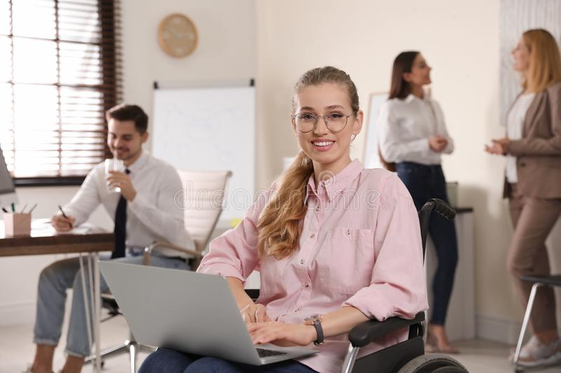 Portrait of woman in wheelchair with laptop and her colleagues royalty free stock photo