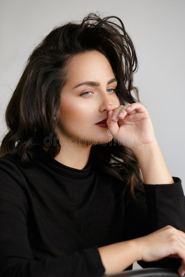 Beauty portrait of a young woman in black, isolated on a white backgorund. Portrait of wonderful young caucasian woman, feeling bad, against white backgorund stock image