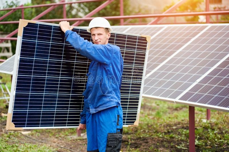 Installation of stand-alone exterior photo voltaic panels system. Renewable green energy generation. Portrait of worker in blue uniform and protective helmet stock images